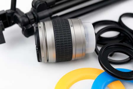 Photo camera lens close-up, with lens protectors and small tripod on white background Stok Fotoğraf