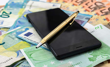 A golden pen on a black mobile phone terminal and euro banknotes in the background Stok Fotoğraf