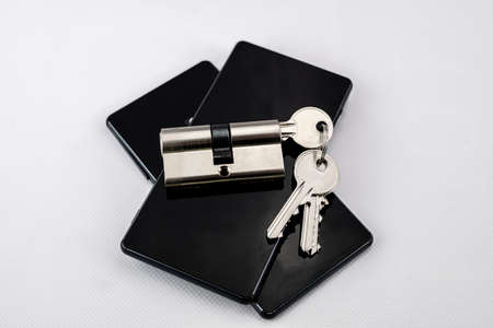 keychain with keys inserted in a lock on two black mobile phones on white background