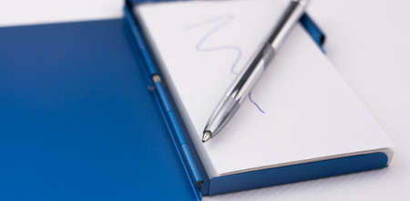 Hold a pen on a notebook to write down ideas and reminders on white paper and blue metal case 写真素材