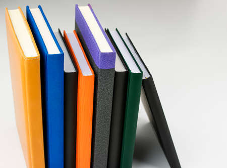 Bookshelf with books of different colors and sizes on white background and placed vertically