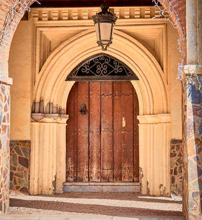 Old entrance door, with gothic arch and wooden gate with cast iron and sculpted iron knocker