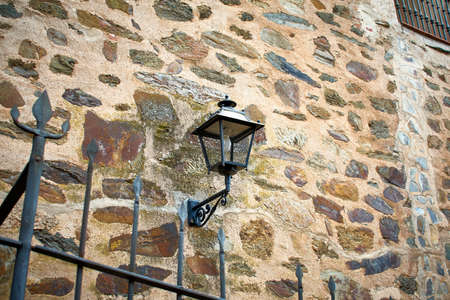 Stone facade with a black cast iron lantern for outdoor lighting. Parador of Guadalupe, west of Spain.