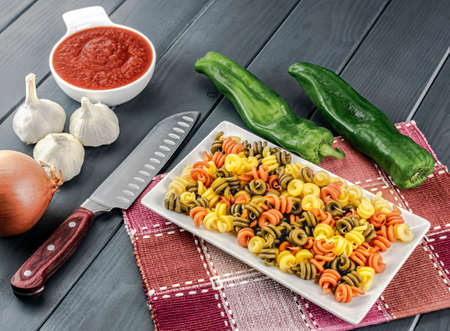 Plate of colorful raw pasta, with its prepared tomato, onion, garlic and green peppers for cutting and cooking