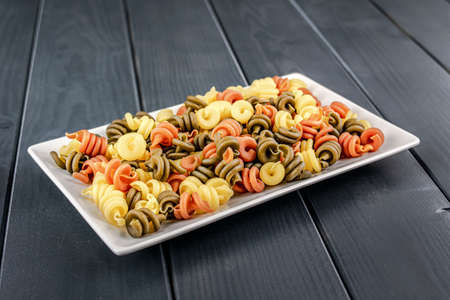 Plate of colorful raw pasta and vegetables ready to be cooked on gray wooden table 写真素材