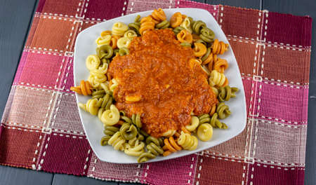 Pasta dish with colorful vegetables, ready to be tasted, with tomato sauce, onion, garlic, green pepper and extra virgin olive oil, on tablecloth and gray wooden table
