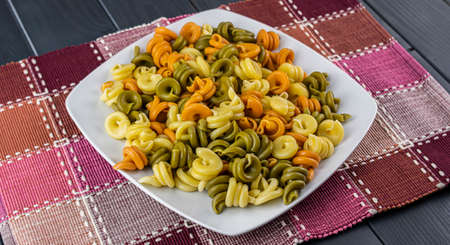 Colorful and vegetable cooked pasta dish ready to be served with tomato and cheese sauce, on gray wooden table
