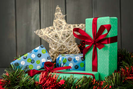Christmas gifts packaged and decorated with wrapping paper and cloth ties, green and red tinsel and gold star on dark wooden background 写真素材