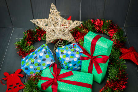 Christmas gifts decorated with red cloth bows, red and green tinsel and shining star with velvet bell on dark wooden background
