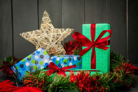 Christmas gifts packaged and decorated with bows, green and red tinsel on wooden background and a golden star