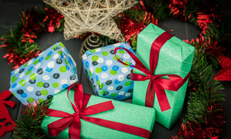 Christmas gifts decorated with bows, red and green tinsel and other decorative elements on dark wooden background