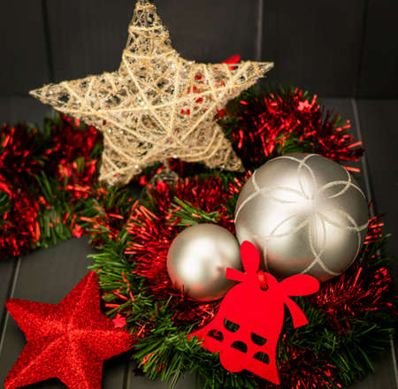 Christmas decoration with gold star and silver balls on red and green tinsel, red velvet bell and star with bright and red glitter with dark wooden background 写真素材