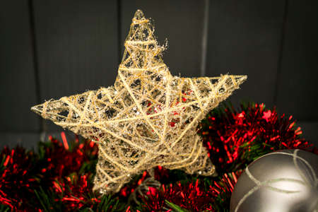 Christmas decoration with golden star and silver ball on red and green tinsel with dark wooden background