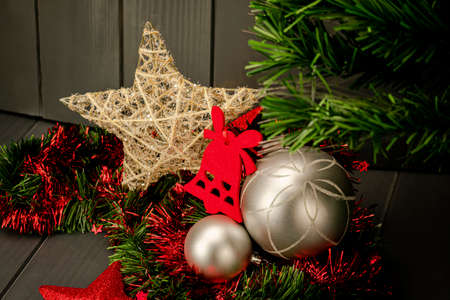 Christmas decoration with silver balls, green and red tinsel, red and gold stars, velvet bell and Christmas tree on dark wooden background 写真素材