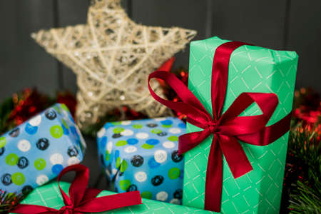 Christmas gifts decorated with red bows and wrapped in wrapping paper, ready to surprise