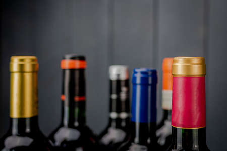 Set of unopened red wine bottle labels from different manufacturers with different color labels on gray wooden background