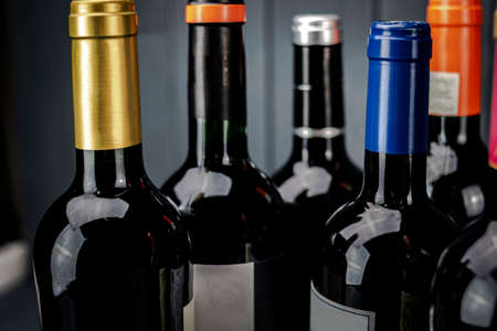 Bottles of red wine grouped with labels of different colors in the foreground on gray background