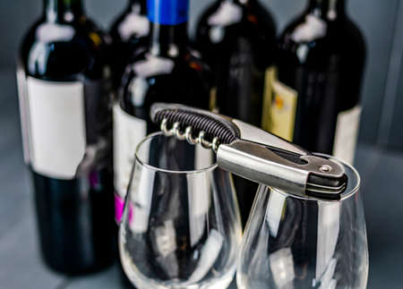 Traditional corkscrew on glass wine glasses and bottles of red wine in the background ready to be opened and tasted
