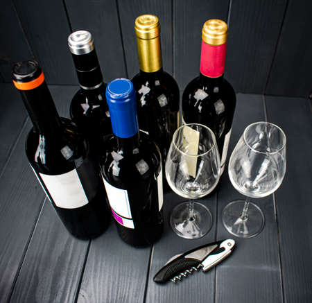 Bottles of red wine from different manufacturers with two sparkling wine glasses and a corkscrew for tasting, in well-lit gray wooden space