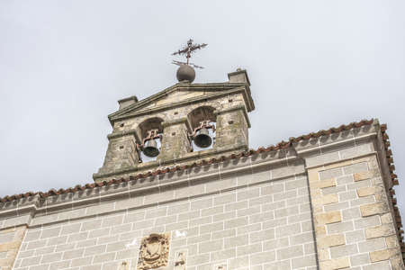 Bell tower of a church with a metal cross on top and details carved in stone on the facade, west of Spain, in Serradilla (Caceres)