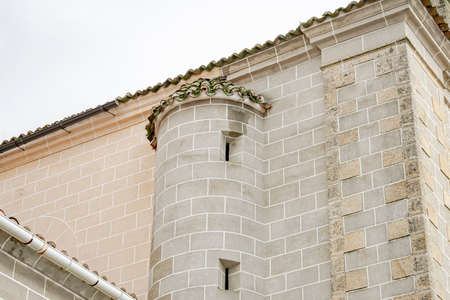 Side facade of a stone church with a rounded ledge to provide space for the building's stairs with openings for aeration and light