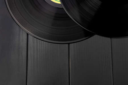 Traditional glossy black vinyl records without scratches on a gray wooden table