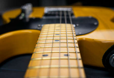 Close-up of the mast, frets and strings of a classic electric guitar, in yellow and black, bright on gray wood