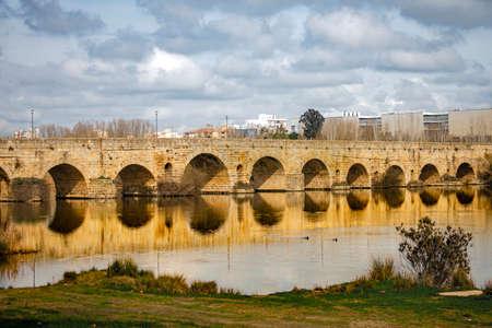 Roman bridge with its arches are reflected on the river on an autumn afternoon