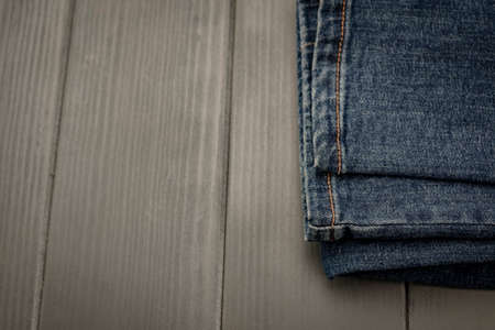 Denim pants with gold stitching on gray wooden background