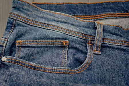Front pockets of a washed blue denim pants