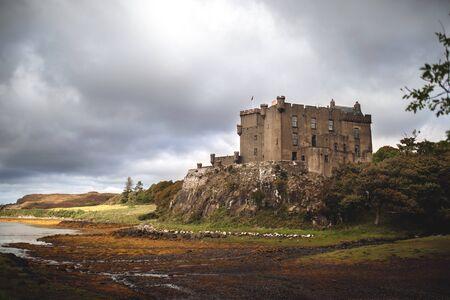 Castillo de Dunvegan con un cielo espectacular y raros rayos de sol que iluminan mágicamente todo alrededor del castillo. Foto de archivo