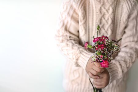Childrens hands hold a bouquet of pink carnations.