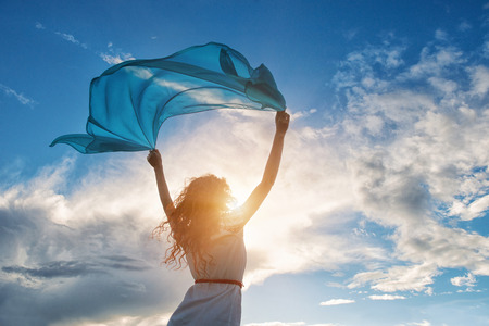 Beautiful young woman on sunset background with blue tissue. 写真素材