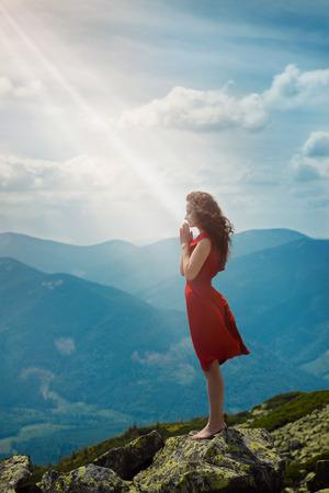orando: Hermosa mujer en vestido rojo de pie en la piedra y orar
