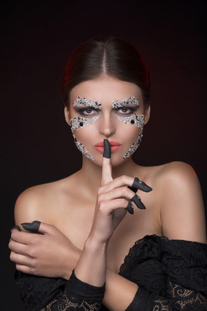 faceart: Beautiful sensual woman looking at camera with face-art make-up and showing silence gesture