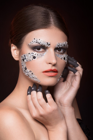 faceart: Beautiful sensual woman looking at camera with face-art make-up and red backlight Stock Photo