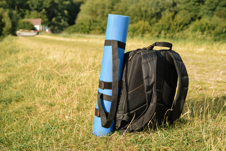 yoga mat: Photo backpack standing in a green  grass with blue yoga mat Stock Photo