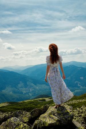 buena postura: Mujer hermosa en el vestido blanco de pie sobre la piedra y quiere volar
