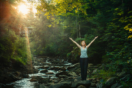 Happy woman enjoying the nature in forest with sunset on background Stock Photo