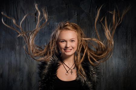 Portrait of sensual blond woman with fluttering dreadlocks. On dark background photo