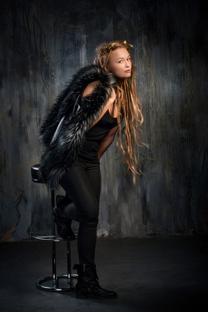 Sensual blond woman with long dreadlocks and holding fur vest. On dark background photo
