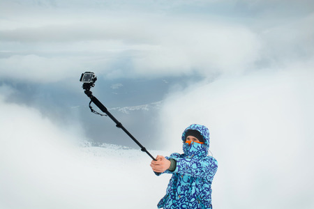 an action: Man taking selfie using action camera at the mountains. Outdoor activities on fresh winter air
