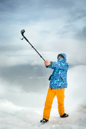 wintersport: I am in the most beautiful place. Snowboarder taking selfie using action camera at the mountains Stock Photo