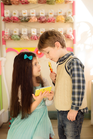 acquaintance: Little girl shows boy how to use tablet. Boy and girl looking at each other