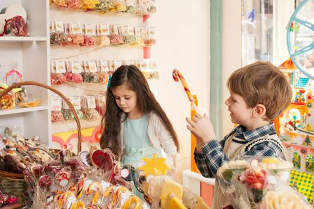 Children choose sweets in the store. Little girl and boy showing candy to each other