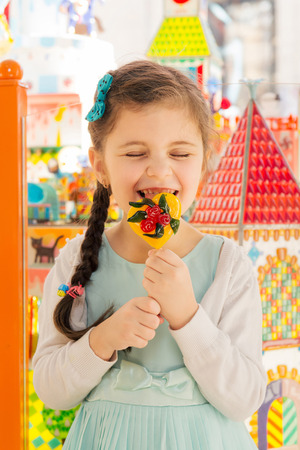 Happy little girl having fun and licking candy