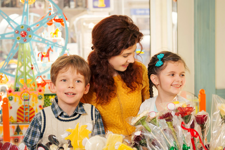 acquaintance: Young mother her son and  daughter in the candy store. Happy children having fun