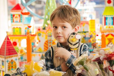 kids' room: Greedy boy strongly holding lollipop in the hands at kids room
