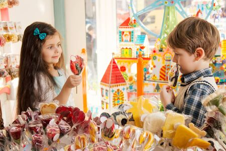 candy store: Little girl and boy showing candy to each other Stock Photo