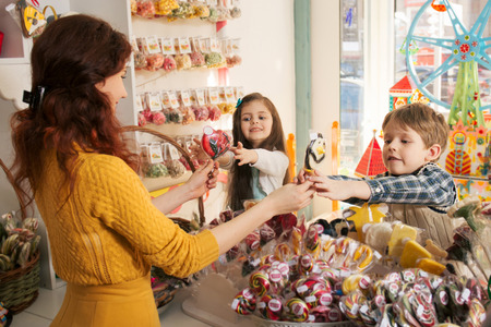 salesman: Happy boy and girl buying sweets in the store. Beautiful woman salesman gives candies to children